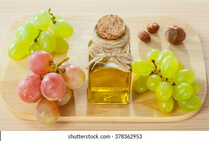 Healthy eating for beautiful skin and strong hair! Fresh grapes, nuts and a bottle of natural oil on wooden board