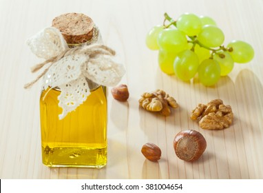 Healthy eating for beautiful skin and strong hair! Fresh grapes, nuts and a bottle of natural oil on wooden background