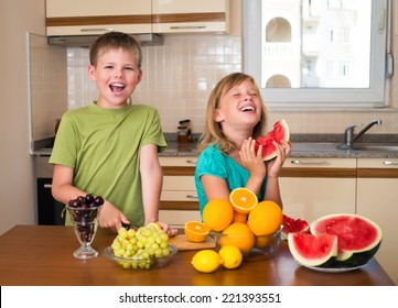 Healthy eating - children eating watermelon. Boy and girl in the kitchen with different kinds of fruits for breakfast food.  Funny playful kids cooking together, help children to parents.