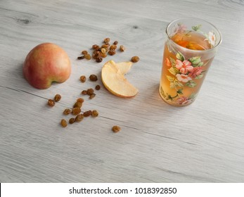 Healthy Eating: Compote of dried fruits. A glass with a drink from dried fruits, an apple, raisins. A curative and preventive drink for colds. Vegetarian food. Diet. Top view. Copy space.