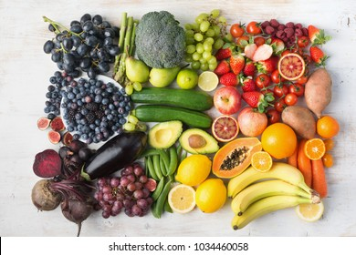 Healthy eating concept, assortment of rainbow fruits and vegetables, berries, bananas, oranges, grapes, broccoli, beetroot background on white table arranged in rectangle, top view, selective focus