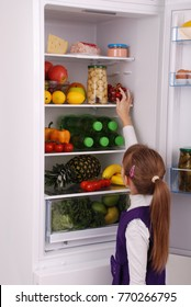 Healthy eating concept. Diet. Beautiful  girl near the Fridge with healthy food. Fruits and vegetables in the refrigerator.