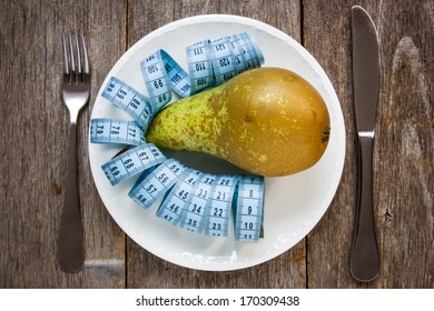 Healthy eating concept. Fresh pear and measurement tape in a plate.