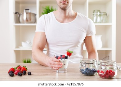 Healthy eating concept. Man with delicious yogurt with fresh berries