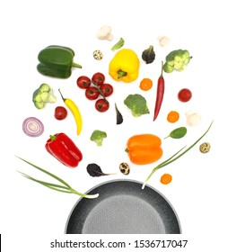 Healthy eating and cooking with various flying chopped vegetables ingredients, pan isolated on white background, top view. Concept diet and healthy eating.