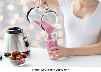 healthy eating, cooking, vegetarian food, dieting and people concept - close up of woman with blender and strawberries pouring milk shake to glass over holidays lights background