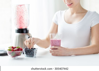 healthy eating, cooking, vegetarian food, dieting and people concept - close up of woman with blender and berries preparing milk shake at home