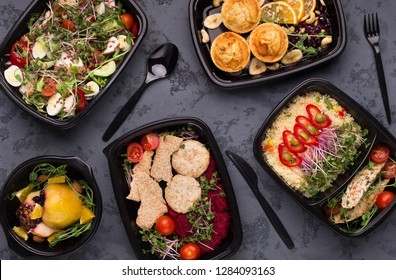 Healthy eating is delicious. Set of various healthy meals in black delivery containers with plastic cutlery, top view