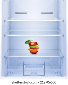 Healthy eating, diet concept. Apples and orange fruit in empty refrigerator.