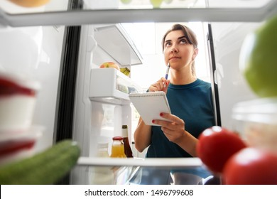 healthy eating and diet concept - woman opening fridge and making list of necessary food at home kitchen