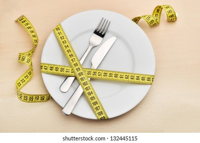 Healthy eating or dieting concept. Empty plate, fork and knife wrapped in measuring tape.
