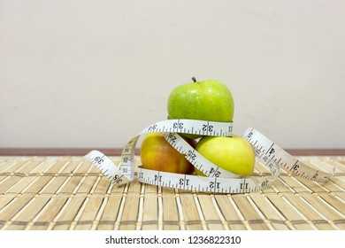 Healthy eating, dieting, slimming and weigh loss concept. Measuring tape around apples on bamboo mat background with copy space.