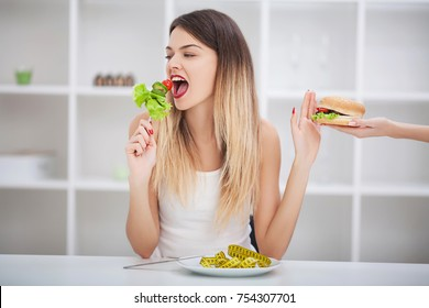 Healthy eating, dieting, slimming and weigh loss concept. Diet. Dieting concept. Weight Loss. The measuring tape is wrapped around the arm. In the other hand is a hamburger. You need to lose weight