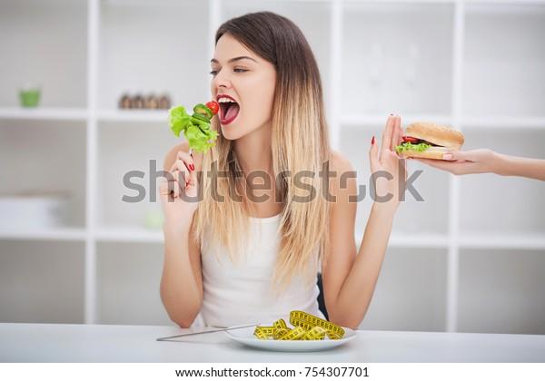 健康的な食事、ダイエット、痩せ衰え、体重減少のコンセプト。ダイエット。ダイエットのコンセプト。減量。測定テープは腕に巻き付けられる。一方、ハンバーガーはハンバーガーです。あなたは痩せる必要がある