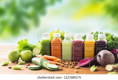 healthy eating, drinks, diet and detox concept - plastic bottles with different fruit or vegetable juices and food on wooden table over green natural background