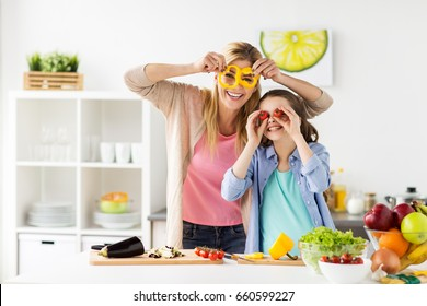 healthy eating, family and people concept - happy mother and daughter cooking vegetables for dinner and having fun at home kitchen