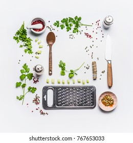 Healthy eating and flavoring ingredients for tasty cooking with spoon and knife on white background, top view, frame, flat lay. Creative layout for detox, vegetarian and clean food concept.