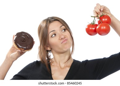 Healthy eating food concept. Woman comparing unhealthy donut and organic red tomatoes, thinking isolated on a white background
