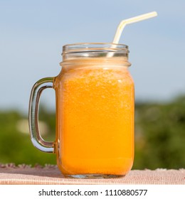 Healthy eating, food, dieting and vegetarian concept - glass mug of juice yellow smoothie shake from carrot juice, lemon, honey and banana in nature background, close up