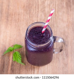 Healthy eating, food, dieting and vegetarian concept - smoothie from mulberry in mug , close up. Fresh mulberry and juice on wooden background