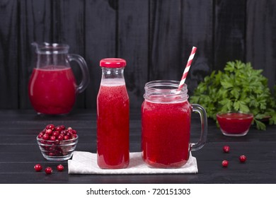 Healthy eating, food, dieting and vegetarian concept - red cranberry juice and raw cranberry on black wooden background, close up