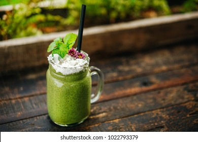 Healthy Eating. Green fresh smoothies mango and spirulina on a wooden table are decorated with flowers and coconut shavings. Fresh dietary tropical drink.