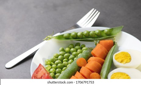 healthy eating green peas, carrots, tomato, cucumber and egg on a white plate