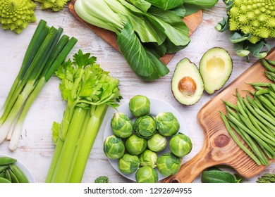 Healthy eating. Green vegetables fruits on white table broccoli sprouts peas avocado courgette beans bok choy celery, top view, selective focus