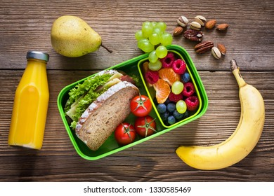 Healthy eating habits concept. School lunch box with sandwich, fruits, vegetables, orange juice and nuts.