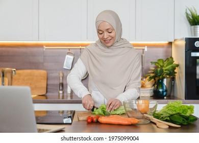 Healthy eating habits, mature muslim islamic wife woman in hijab cooking preparing vegetable salad using laptop as a tutorial for recipes online. Vegan vegetarian food