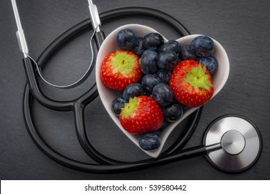 Healthy eating and heart health concept with a heart shaped bowl with blueberries and a stethoscope each blueberry is packed full of vitamins and antioxidants that can prevent coronary heart disease