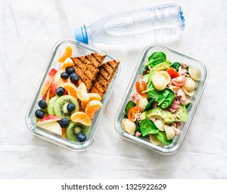 Healthy eating lifestyle concept. Office food lunch box - sweet and savory lunch, snack and clean water. Pasta, tuna, spinach, avocado salad and fruit, peanut butter sandwiches lunch box