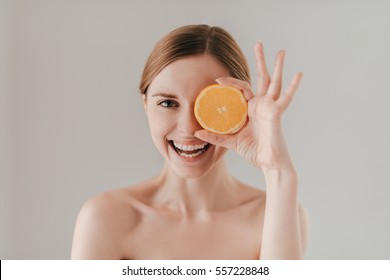 Healthy eating makes you beautiful. Attractive young woman with freckles on face holding orange slice and smiling while standing against background