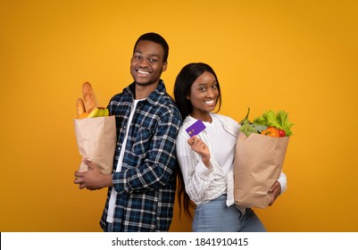 Healthy eating, modern lifestyle and grocery shopping. Cheerful millennial african american couple in casual hold paper bags with food and show credit card isolated on yellow background, studio shot