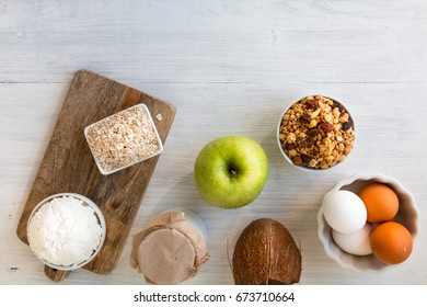 Healthy eating products on white wooden table - cottage cheese, milk, coconut milk, muesli, eggs, apple, fruits, flakes, cereal, granola, yoghurt. Top view. Copy space.