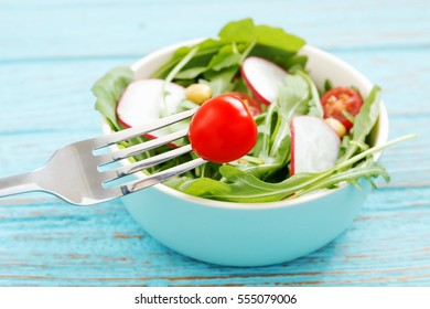 Healthy eating with salad closeup tomato with hand holding fork