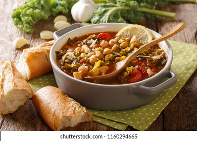 Healthy eating: a thick soup of chickpeas, kale, tomatoes, garlic and potatoes with lemon close up in a bowl on the table. horizontal