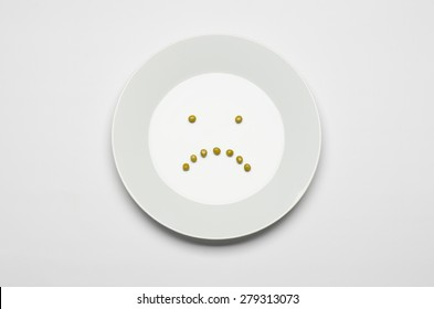 Healthy eating topic: green peas lying on a white plate on a white table in the studio, a sad smile top view
