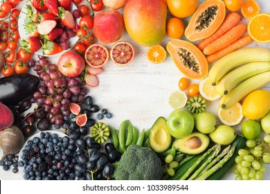 Healthy eating, varieity of fruits and vegetables in rainbow colours on the off white table arranged in a frame with copy space, vertical top view, selective focus