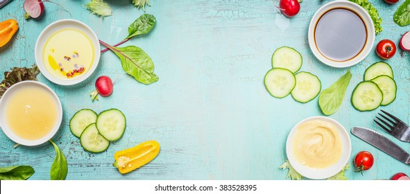 Healthy Eating with vegetables salad ingredients, dressing  and cutlery on turquoise blue shabby chic background, top view, banner. Healthy lifestyle or diet food concept