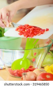 Healthy eating, vegetarian food, cooking, dieting and people concept. Woman in kitchen at home preparing fresh salad slicing vegetables throwing red pepper into bowl