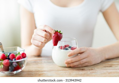 healthy eating, vegetarian food, diet and people concept - close up of woman hands with yogurt and berries on table