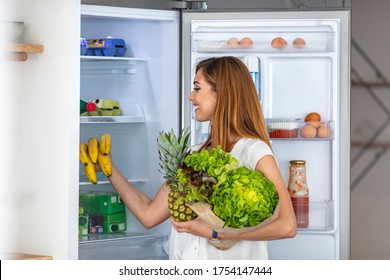 Healthy eating woman grabbing vegetables from the fridge. Healthy eating woman. Woman looking inside the refrigerator and picking up healty food. Woman Come to the Kitchen with Fresh Groceries