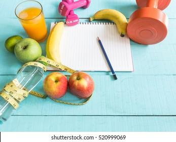 Healthy eating ,Workout and fitness dieting ,fitness and weight loss concept, tape measure, banana, apple, fruit and water bottle, blank copy space notebook,top view on wooden background