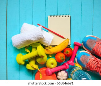 Healthy eating ,Workout and fitness dieting ,fitness and weight loss concept, fruit, Vegetable and water bottle,notebook,top view on blue wooden background