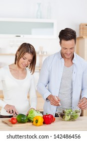 Healthy eating with a young couple preparing salad in the kitchen using farm fresh ingredients