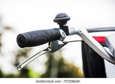 Healthy, ecological transport concept. close-up bike handlebar, brake lever and bell of a bicycle rental over blurred city