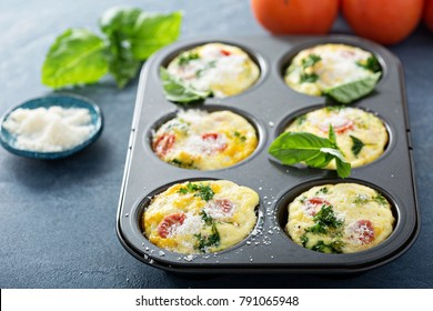 Healthy egg muffins, mini frittatas with tomatoes and greens topped with grated parmesan