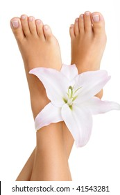 Healthy and elegant well-groomed female feet with the flowers on a white background