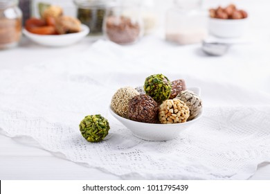 Healthy energy balls made of dried fruits and nuts with coconut chips, flax seeds, pistachios, sesame. Raw vegan candy.